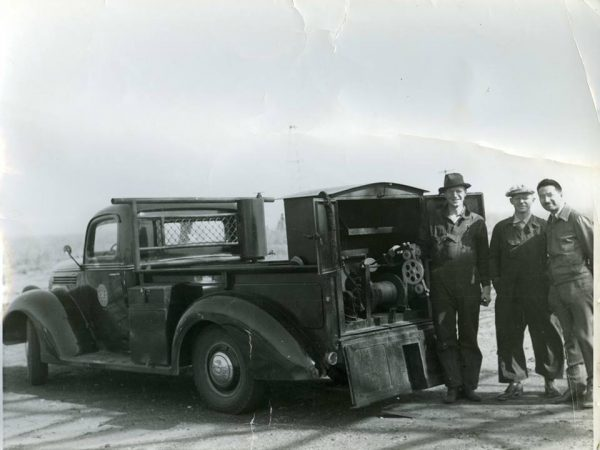 Men posed at the back of an old-time wireline truck, facing the camera.