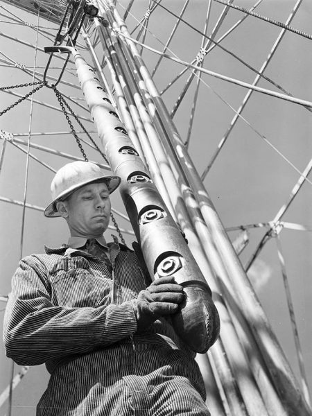 Wireline History: rig worker positions a perforating gun over a wellbore.