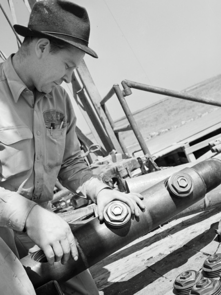 Wireline history: A Lane Wells worker examines a perforating gun.