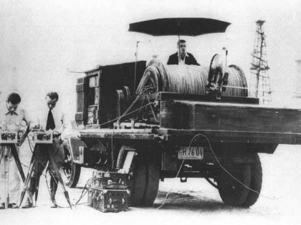 An early-model wireline truck with an umbrella atop.
