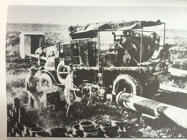Early model wireline truck in action, with crew